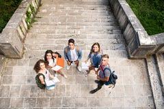 Studenti adolescenti ai punti di pietra davanti all'università Immagine Stock