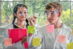 Studenti adolescenti che disegnano immagine delle idee su un bordo di vetro fotografie stock