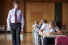 Studenti adolescenti che si siedono esame con l'insegnante Invigilating fotografia stock