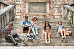 Studenti adolescenti con gli aggeggi fuori sui punti di pietra Immagine Stock