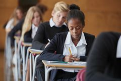 Studenti adolescenti nell'esame di seduta dell'uniforme a scuola Corridoio fotografia stock