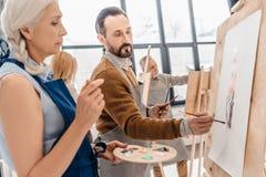 studenti adulti maschii e femminili che dipingono insieme Fotografie Stock