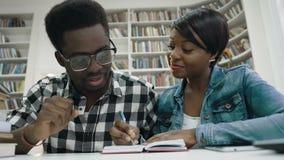 Studenti africani che fanno una certa nota nel taccuino in biblioteca stock footage