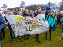 Studenti all'anti protesta del mutamento climatico a L'aia con le insegne che camminano attraverso la città immagine stock