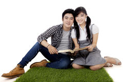 Studenti asiatici con il libro su erba Immagini Stock Libere da Diritti