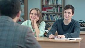 Studenti attentamente che ascoltano l'insegnante maschio e che comunicano nell'aula archivi video