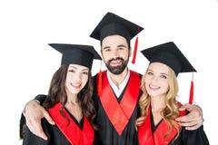Studenti in cappucci accademici che stanno abbraccianti e sorridenti alla macchina fotografica Fotografia Stock