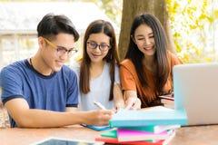 Studenti che aiutano amico a consultarsi, istitutore, lavoro di squadra fotografia stock libera da diritti
