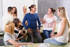 Studenti che chiacchierano e che sorridono all'istituto universitario Immagini Stock