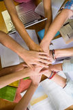 Studenti che dispongono insieme le mani sopra la tavola delle biblioteche Immagine Stock