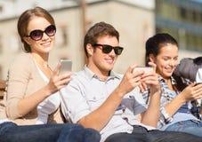 Studenti che esaminano gli smartphones ed il pc della compressa Fotografia Stock