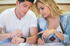 Studenti che esaminano orologio mentre studiando Immagine Stock