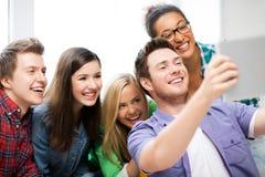 Studenti che fanno immagine con il pc della compressa alla scuola Fotografie Stock Libere da Diritti