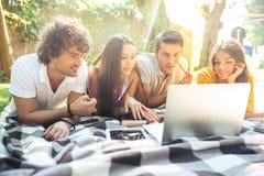 Studenti che fanno insieme compito sul computer portatile Immagini Stock