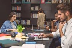 Studenti che fanno progetto del gruppo nella biblioteca della città universitaria Immagini Stock