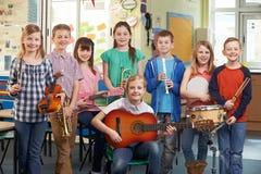 Studenti che giocano insieme nell'orchestra della scuola immagini stock libere da diritti