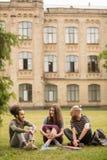 Studenti che hanno conversazione vivace che si siede sul prato inglese Fotografie Stock Libere da Diritti
