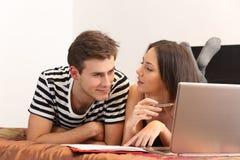 Studenti che imparano a casa con un computer portatile e le note Fotografia Stock Libera da Diritti