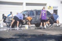 Studenti che lavano le automobili per una raccolta fondi della scuola, nanometro immagine stock libera da diritti