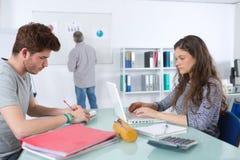 Studenti che lavorano allo scrittorio mentre insegnante alla lavagna Fotografia Stock Libera da Diritti