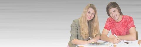 Studenti che lavorano davanti al fondo vago Fotografia Stock