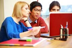 Studenti che lavorano insieme al computer portatile Fotografia Stock Libera da Diritti