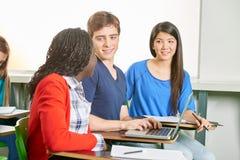 Studenti che lavorano nel gruppo con un computer portatile Fotografia Stock Libera da Diritti