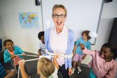 Studenti che legano un insegnante con la corda in aula Fotografie Stock