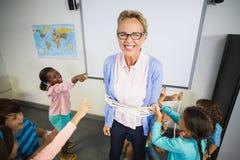 Studenti che legano un insegnante con la corda in aula Fotografie Stock Libere da Diritti