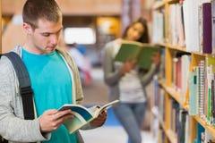 Studenti che leggono dallo scaffale per libri nella biblioteca Fotografia Stock