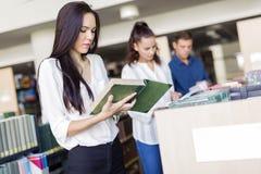 Studenti che leggono e che studiano nella biblioteca Fotografia Stock