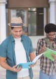 Studenti che leggono i risultati dell'esame davanti alla porta della costruzione Immagine Stock Libera da Diritti