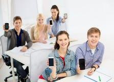 Studenti che mostrano gli schermi in bianco neri dello smartphone Immagine Stock