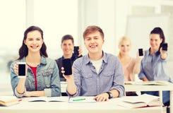 Studenti che mostrano gli schermi in bianco neri dello smartphone Immagine Stock Libera da Diritti