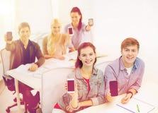 Studenti che mostrano gli schermi in bianco neri dello smartphone Fotografie Stock