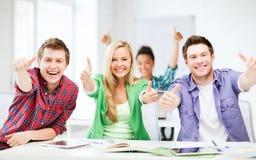 Studenti che mostrano i pollici su alla scuola Immagini Stock