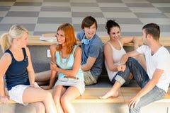Studenti che parlano seduta sul banco della scuola Immagini Stock Libere da Diritti