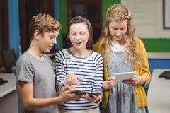 Studenti che per mezzo del telefono cellulare e della compressa digitale Fotografia Stock