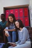Studenti che per mezzo del telefono cellulare e della compressa digitale sulla scala Fotografie Stock