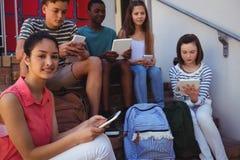 Studenti che per mezzo del telefono cellulare e della compressa digitale sulla scala Immagine Stock