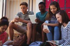 Studenti che per mezzo del telefono cellulare e della compressa digitale sulla scala Immagini Stock