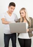 Studenti che per mezzo di un computer portatile Fotografia Stock Libera da Diritti