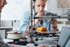Studenti che per mezzo di una stampante 3D Fotografie Stock Libere da Diritti