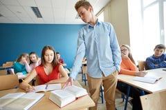 Studenti che pettegolano dietro la parte posteriore del compagno di classe alla scuola fotografia stock libera da diritti