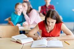 Studenti che pettegolano dietro la parte posteriore del compagno di classe alla scuola Immagine Stock