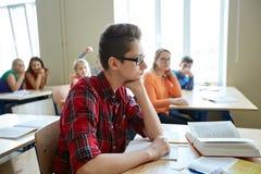 Studenti che pettegolano dietro la parte posteriore del compagno di classe alla scuola Fotografie Stock