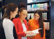 Studenti che preparano insieme per gli esami nella biblioteca Immagini Stock