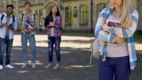 Studenti che ridono e che indicano la ragazza triste sola che sta da parte, bulling crudele stock footage