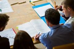 Studenti che scrivono le note nella biblioteca di istituto universitario Immagini Stock Libere da Diritti