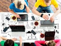 Studenti che si siedono alla tavola facendo uso dei computer e delle compresse Fotografia Stock Libera da Diritti